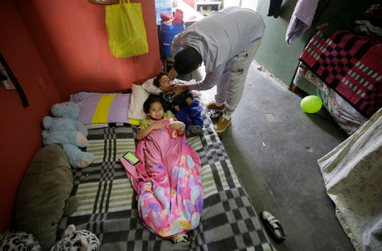 Honduran asylum seeker Francisco Echevarria tends to his children at the Pasos de Fe Migrant Shelter in Juarez Tuesday as the family waits for another hearing in El Paso.