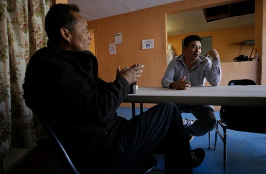 Pasos de Fe shelter director Miguel Gonzalez, left, sits with Honduran asylum seeker Francisco Echevarria at the Juárez shelter.