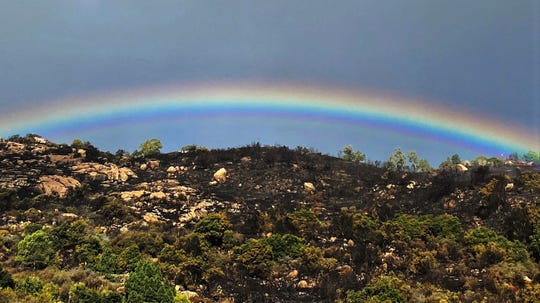 With some areas still smoldering below, a rainbow appears above the burn scar near Painted Cave Road on Wednesday morning.