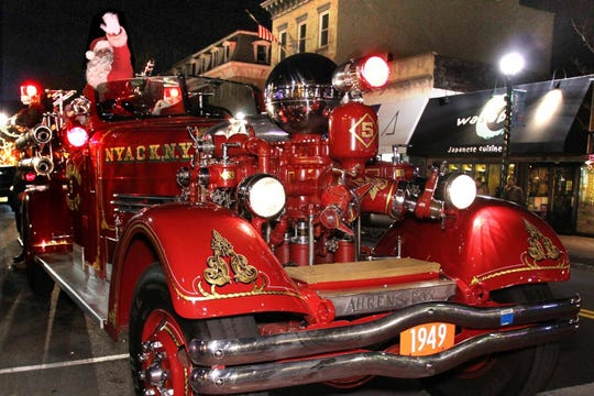 An old-school firetruck makes its way down a Nyack street with Santa Claus in 2018.