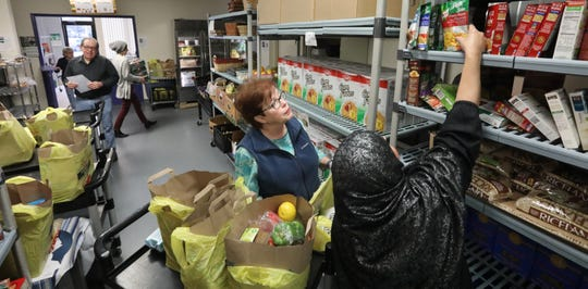 Marge Murphy of Orangeburg helps people pick out free items from the food pantry at People to People in West Nyack Nov. 27, 2019.