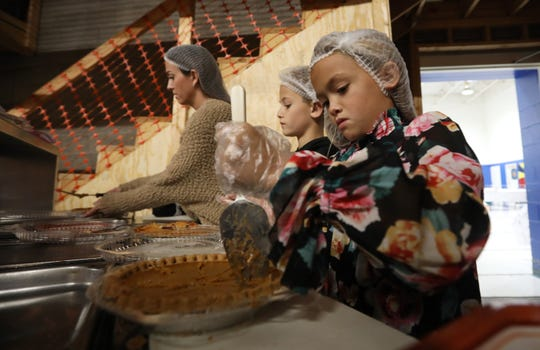 Isabella Lombardy, 8, her brother Nick, 10, and mother Jen prepare pies for serving at the Salvation Army Thanksgiving dinner Wednesday.