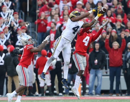 Michigan wide receiver Nico Collins catches a pass over Ohio State safety Jordan Fuller during their game in 2018.