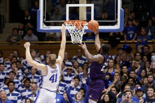 Stephen F. Austin forward Nathan Bain drives for the game-winning basket over Duke forward Jack White.