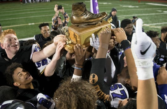 Members of the Cherry Hill West High School football team hoist the Al DiBart Memorial Trophy, which is presented to the winner of the annual Cherry Hill West vs. Cherry Hill East football game, after Cherry Hill West defeated Cherry Hill East, 19 -7, at Cherry Hill West High School on Wednesday, November 27, 2019.
