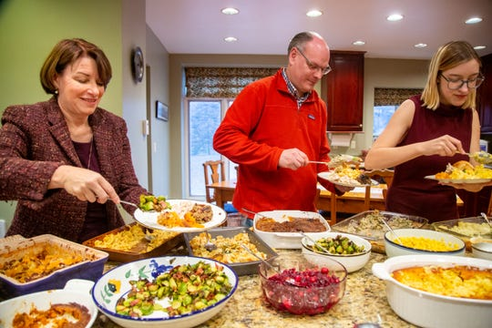 Sen. Amy Klobuchar D-Minn., her husband John D. Bessler and their daughter Abigail Klobuchar Bessler make plates for Thanksgiving at the home of her campaignÕs state chairwoman Andy McGuire Thursday, Nov. 28, 2019.