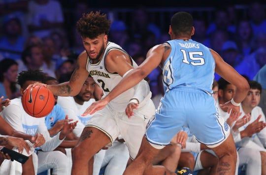 Michigan forward Isaiah Livers dribbles as North Carolina forward Garrison Brooks defends during the first half in the Bahamas, Nov. 28, 2019.