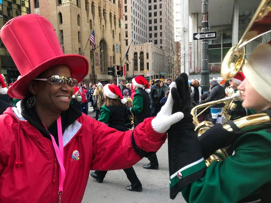 Thanksgiving Day parade marshal Myla Harris of Canton Township slaps high fives with a sousaphone player in the Dakota High School band from Macomb Township on Nov. 28, 2019.