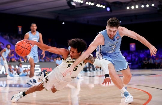 Michigan guard Eli Brooks and North Carolina guard Andrew Platek go for a loose ball during the first half in the Bahamas, Nov. 28, 2019.