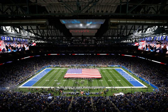 A large American flag displayed on the field during the national anthem before the game between the Detroit Lions and the Chicago Bears, Thursday, Nov. 28, 2019, in Detroit.