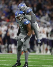 Detroit Lions defensive end Trey Flowers (90) and safety Tavon Wilson (32) celebrate his sack vs. the Chicago Bears during the second half Thursday, Nov. 28, 2019 at Ford Field.