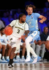 Michigan guard Zavier Simpson dribbles as North Carolina guard Cole Anthony defends during the first half in the Bahamas, Nov. 28, 2019.
