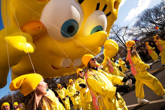 Balloon handlers hold SpongeBob Square Pants balloon close to the ground as strong winds affect the Macy's Thanksgiving Day Parade, Thursday, Nov. 28, 2019, in New York.