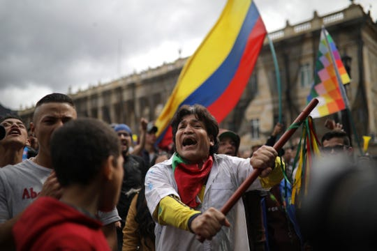 An anti-government protester chants during a demonstration in Bogota, Colombia, Wednesday, Nov. 27, 2019.