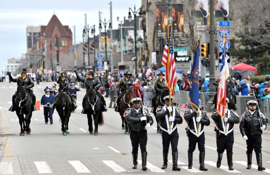 Members of the Detroit Police Color Guard lead the parade, followed by the mounted unit, as thousands attend America's Thanksgiving Parade on Woodward in Detroit in November.