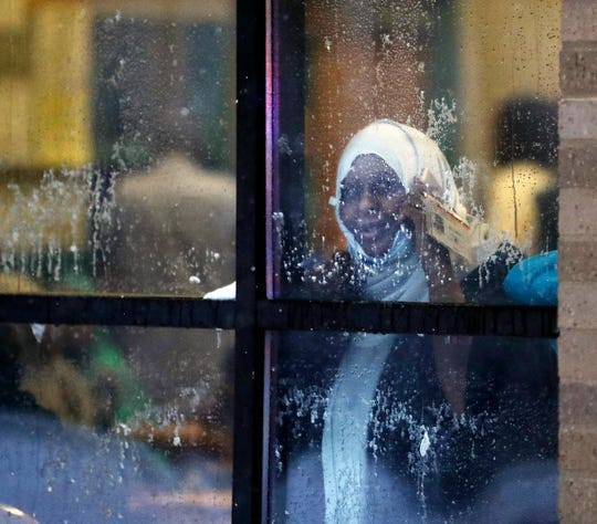A displaced resident looks out a window after a deadly fire at a high-rise apartment building Wednesday, Nov. 27, 2019, in Minneapolis.