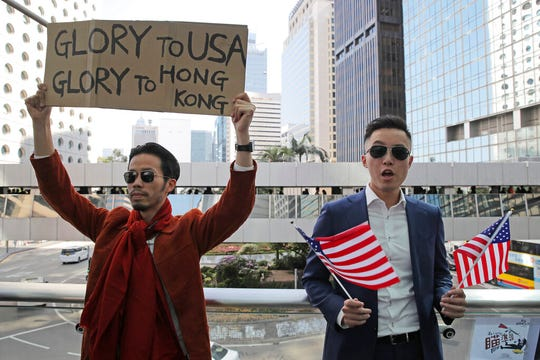 Protesters hold American flags and placard during a demonstration in Central, the financial district of Hong Kong, Thursday, Nov. 28, 2019. China reacted furiously to President Donald Trump's signing of two bills on Hong Kong human rights and said the U.S. will bear the unspecified consequences.