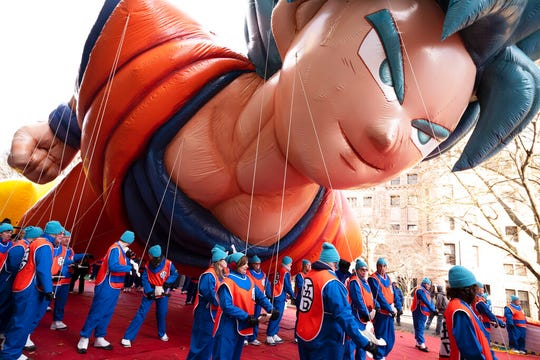 Balloon handlers hold Goku balloon close to the ground as strong winds affect the Macy's Thanksgiving Day Parade, Thursday, Nov. 28, 2019, in New York.