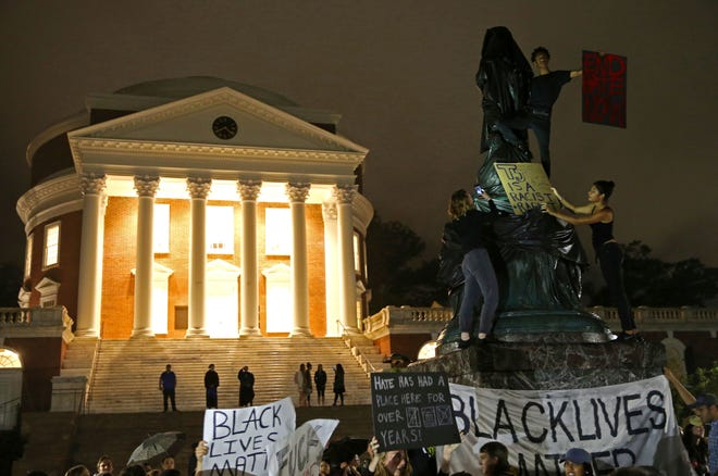 """FILE - In this Sept. 12, 2017, file photo, protesters cover a statue of Thomas Jefferson with black tarp and hold signs up in front of the Rotunda at the University of Virginia for the one month anniversary of the """"Unite the Right"""" rally in Charlottesville, Va."""