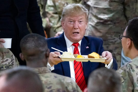 President Donald Trump holds up a tray of Thanksgiving dinner during a surprise Thanksgiving Day visit to the troops, Thursday, Nov. 28, 2019, at Bagram Air Field, Afghanistan.