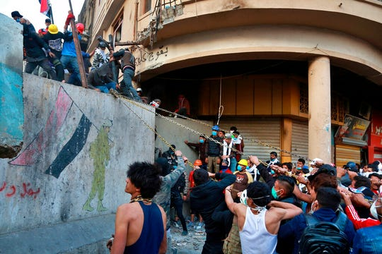 Demonstrators try to pull down concrete walls placed by Iraqi security forces to close in the historic Rasheed Street during clashes between security forces and anti-government protesters in Baghdad, Iraq, Sunday, Nov. 24, 2019. Hundreds of people have died since demonstrations began Oct. 1, when thousands of Iraqis, mostly youth, took to the streets to decry corruption and poor services.