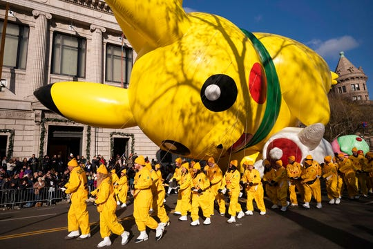 Balloon handlers hold Pikachu close to the ground as strong winds affect the Macy's Thanksgiving Day Parade.