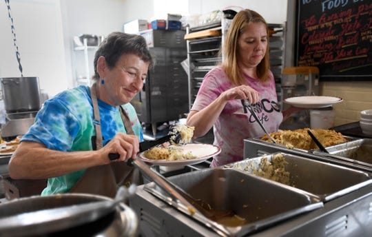 Jan Egan, left, an assistant chef volunteer, serves food along with Yolanda Parten, the operations manager, as they serve a Thanksgiving lunch at FoCo Cafe in Fort Collins, Colo. on Thursday, Nov. 28, 2019.