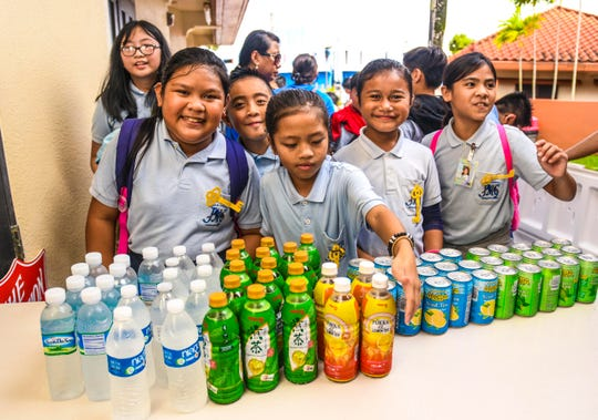 Students of Juan M. Guerrero Elementary School volunteer their holiday morning to serve donated drinks to attendees during The Salvation Army's 23rd annual Thanksgiving Luncheon, for members of the island's disadvantaged community and others, at the main pavilion of the Chamorro Village in Hagåtña on Thursday, Nov. 28, 2019.