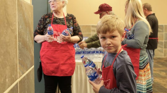 Rylan Clow greeted community members with bottles of water at The Salvation Army's annual Thanksgiving luncheon at the Farmington Civic Center on Thanksgiving Day, Nov. 28, 2019.