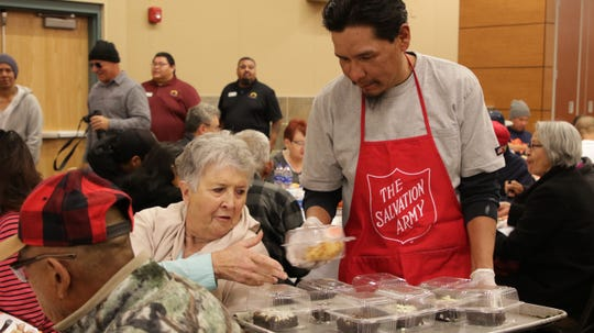 Volunteer Fabian Nargo hands out dessert to Sandy Eastep at The Salvation Army's annual Thanksgiving luncheon at the Farmington Civic Center on Thanksgiving Day, Nov. 28, 2019.