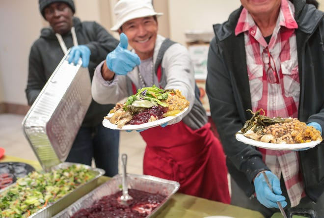 Volunteer Oscar Delarosa, center, prepares plates of food for guests during Well in the Desert's free Thanksgiving meal at Our Lady of Solitude Church in Palm Springs, Nov. 28, 2019.