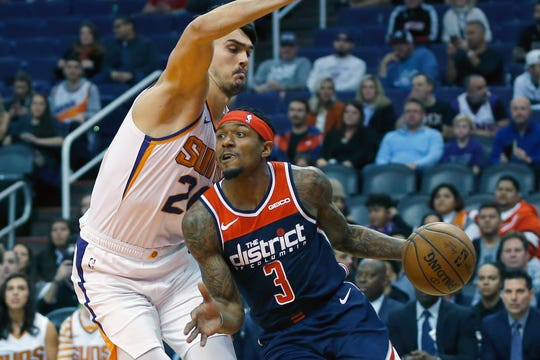 Washington Wizards guard Bradley Beal (3) drives past Phoenix Suns forward Dario Saric in the first half during an NBA basketball game, Wednesday, Nov. 27, 2019, in Phoenix. (AP Photo/Rick Scuteri)