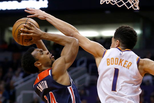 Phoenix Suns guard Devin Booker (1) pressures Washington Wizards guard Ish Smith (14) in the first half during an NBA basketball game, Wednesday, Nov. 27, 2019, in Phoenix. (AP Photo/Rick Scuteri)