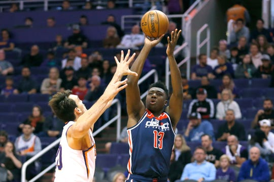 Washington Wizards center Thomas Bryant (13) shoots over Phoenix Suns forward Dario Saric in the first half during an NBA basketball game, Wednesday, Nov. 27, 2019, in Phoenix. (AP Photo/Rick Scuteri)