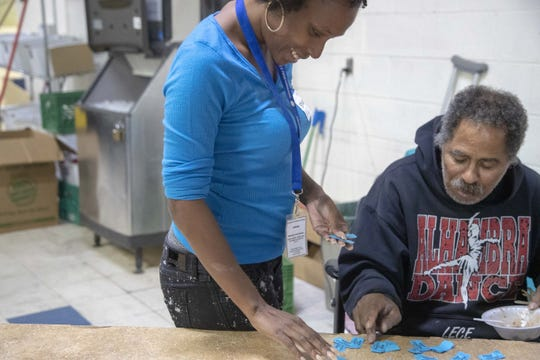 Volunteer Sharelle Countz helps Wayne Powell during the Thanksgiving dinner at St. Vincent de Paul in Phoenix.