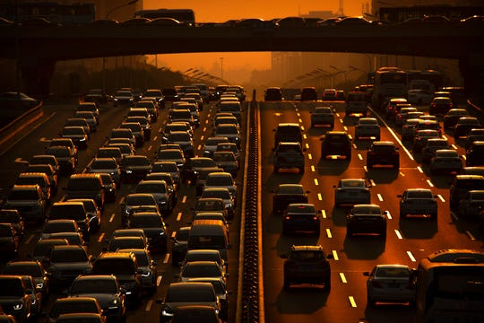 File - In this Friday, Sept. 6, 2019 file photo, commuters make their way along an expressway during rush hour in Beijing. According to Chinese state media, the average concentration of PM2.5 fine air pollutants in Beijing in August was at the lowest level ever recorded for that month. Inger Andersen, head of the U.N. Environment Program, says the world needs 'quick wins to reduce emissions as much as possible in 2020.' Ahead of a global climate summit in Madrid next week, her agency published a report Tuesday showing the amount of planet-heating gases released into the atmosphere hitting a new high last year. (AP Photo/Mark Schiefelbein, file)