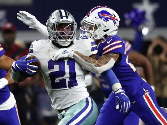 ARLINGTON, TEXAS - NOVEMBER 28:  Ezekiel Elliott #21 of the Dallas Cowboys runs the ball against Taron Johnson #24 of the Buffalo Bills in the first quarter at AT&T Stadium on November 28, 2019 in Arlington, Texas. (Photo by Ronald Martinez/Getty Images)