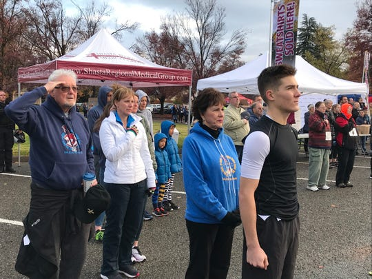 Jack Masterson, right, stands at attention during the singing of the National Anthem before the start of the 2019 Turkey Trot in Redding on Thanksgiving Day. His grandmother, Lyn Davis, stands behind him, in blue. His grandfather, PC Davis, salutes while his aunt, Traci Bilas, sings.