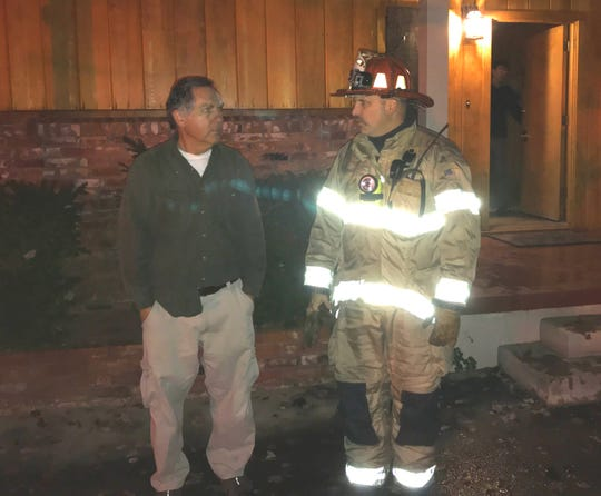 Riverland Drive resident Steve Courtney talks with Redding Fire Department Capt. Ryan Hoberg after firefighters were called to Courtney's home when it was hit by lightning on Wednesday evening, Nov. 27, 2019.