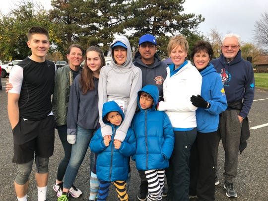 Jack Masterson, 18, left, is hugged by his mom, Jen Masterson, and flanked by other relatives at the 2019 Redding Turkey Trot.  Jack is now a freshman at the U.S. Naval Academy in Maryland.