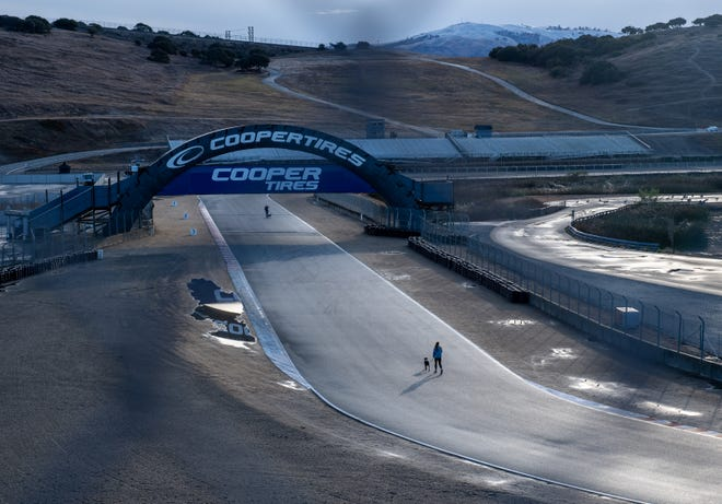 A person walking their dog near the cooper tires sign for the 7th Annual Turkey Trot at Weather Tech Raceway Laguna Seca on Nov. 28, 2019.