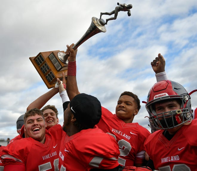 Vineland's Tyreem Powell holds up The Daily Journal Victory Cup after defeating Millville 27-26 at Wheaton Field on Thanksgiving Day, Thursday, Nov. 28, 2019.