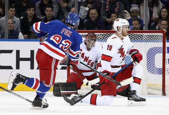 Goalie Petr Mrazek #34 and Dougie Hamilton #19 of the Carolina Hurricanes looks to block a shot by Adam Fox #23 of the New York Rangers during the first period at Madison Square Garden on Nov. 27, 2019 in New York City.