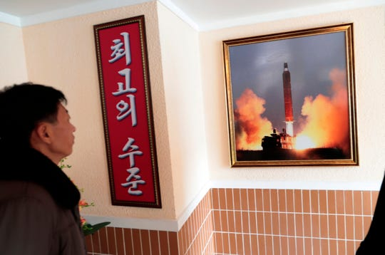 """A photo of the launch of a missile hangs in a factory workers' dormitory in Pyongyang, North Korea. The sign reads """"Highest level."""""""