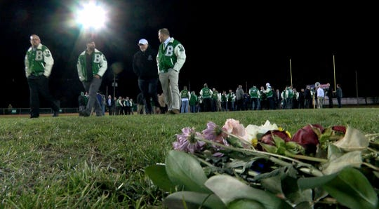 Flowers rest on the 50 yard line as former players and coaches gathered on the Brick High School footall field to honor Warren Wolf Friday evening, November 29, 2019.