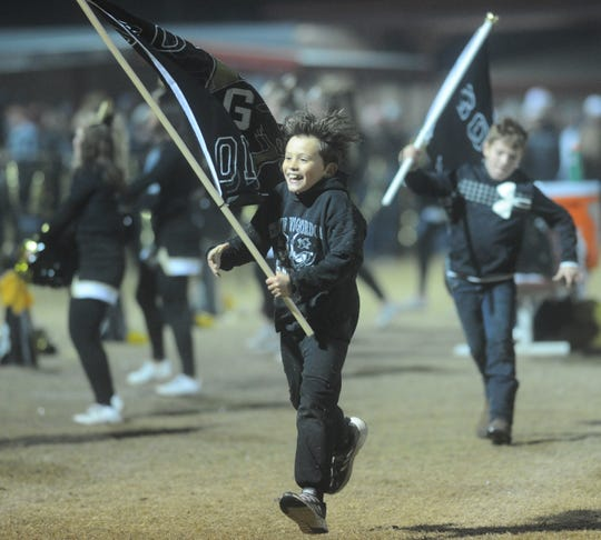 Young Gordon fans run with team flags during Thursday playoff game against Strawn at Hico.