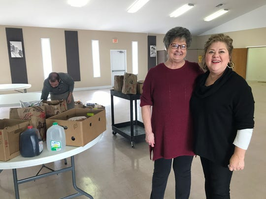 Joann Rice and Susie Honeycutt stand beside one of the meals delivered to 105 homes across the county during the eighth annual Thanksgiving distribution Nov. 27.