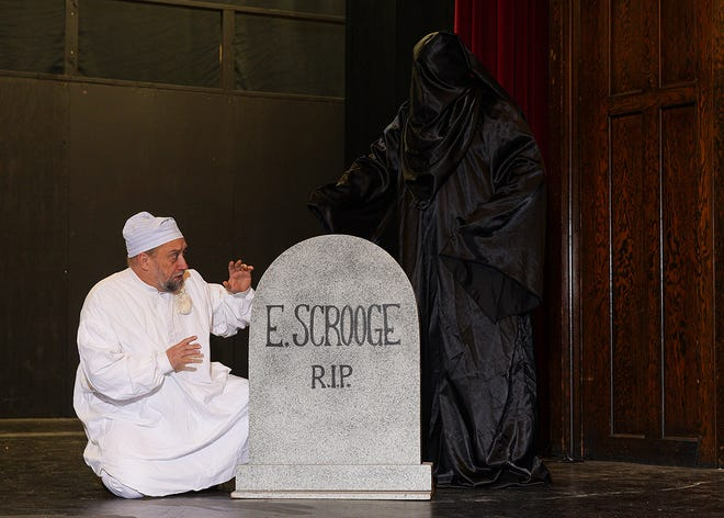 Scrooge (Scott Snively) sees the writing on the wall ... er, gravestone.