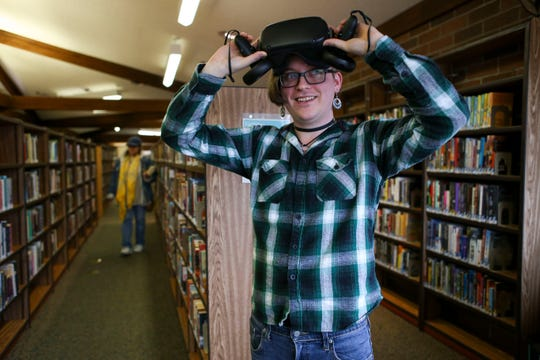 Skye McClure looks out from the Oculus Quest virtual reality headset at Kitsap Regional Library.
