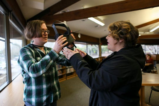 Megan Burton, Kitsap Regional Library employee, hands an Oculus Quest virtual reality headset to Skye McClure, who is developing their own VR battle racing game.